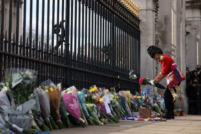 Seorang anggota militer meninggalkan bunga bersama dengan penghormatan lainnya untuk Pangeran Philip di depan gerbang Istana Buckingham.