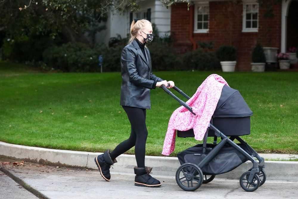 Sophie Turner Kenakan Masker, Blazer Kulit dan Sepatu Bot Louis Vuitton Ketika Berjalan-jalan dengan Sang Putri